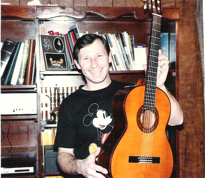 Holding his Spanish Classical guitar in front of a bookcase he made